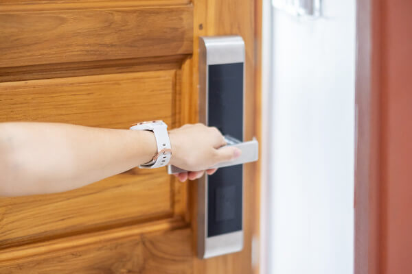 A hand open a safety door and smart lock in Malaysia.